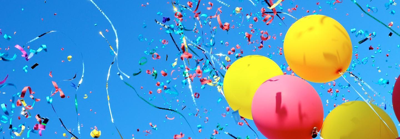 Luftballons, Luftschlangen, Konfetti vor blauem Himmel