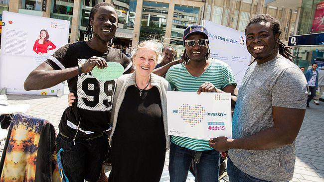 Drei Männer mit einer Frau in der Mitte halten ein Schild hoch: We love Diversity.