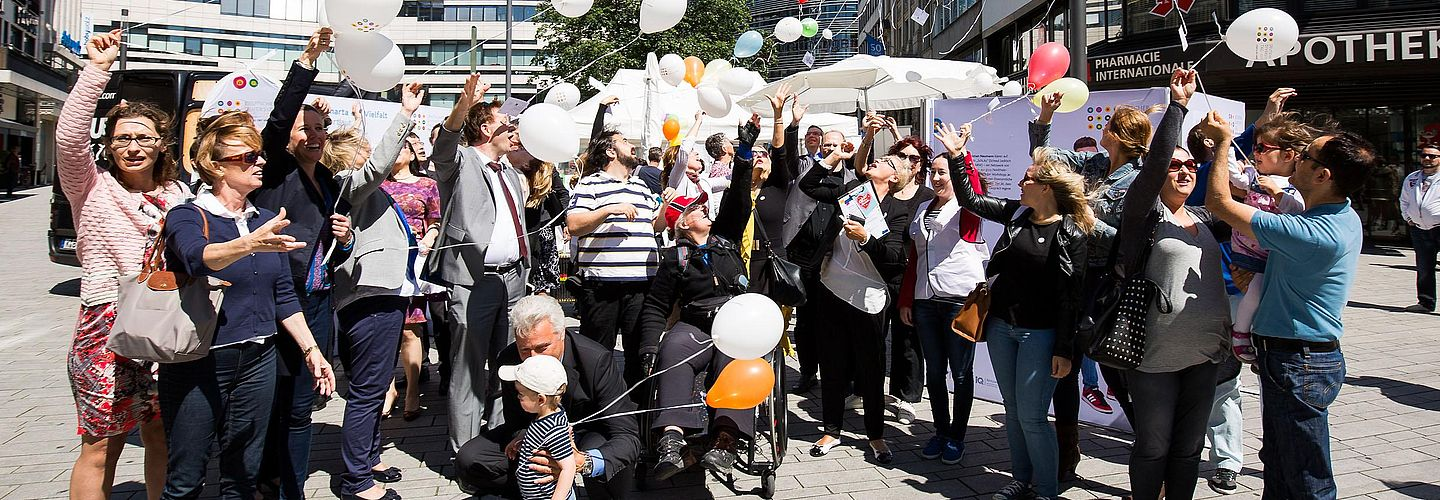 A group of persons with balloons.