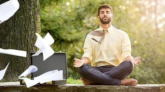 Meditierender Mann neben Koffer, aus dem Papier fliegt